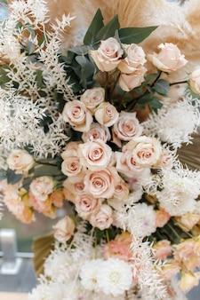 Floristische zusammensetzung von cremerosen, eukalyptuszweigen, pampasgras und dahlie. blumenhintergrund für hochzeitseinladung oder grußkarte. boho-stil