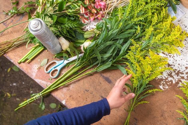 Floristischer arbeitstisch. florist bei der arbeit, die blumenstrauß am blumenladen schafft. ansicht von oben