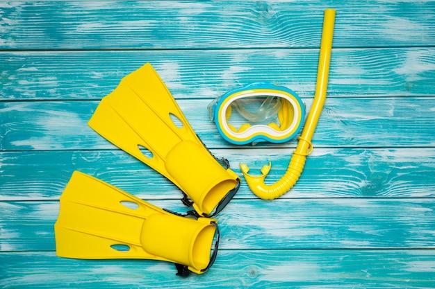 Flossen, brille und schnorchel liegen auf dem brett