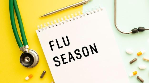 Flu season steht in einem notizbuch auf einer farbtabelle neben pillen und einem stethoskop. medizinisches konzept