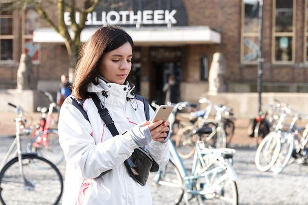 Flucht in eine stadt. junge frau der ethnischen zugehörigkeit im frühjahr, die ein telefon benutzt, um sich auf straßen zu führen.