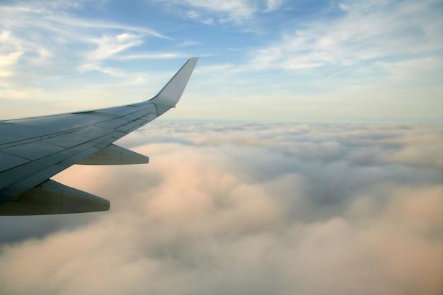 Flügel der rechten seite des flugzeugs, flugzeug, das über wolken in einem blauen himmel fliegt