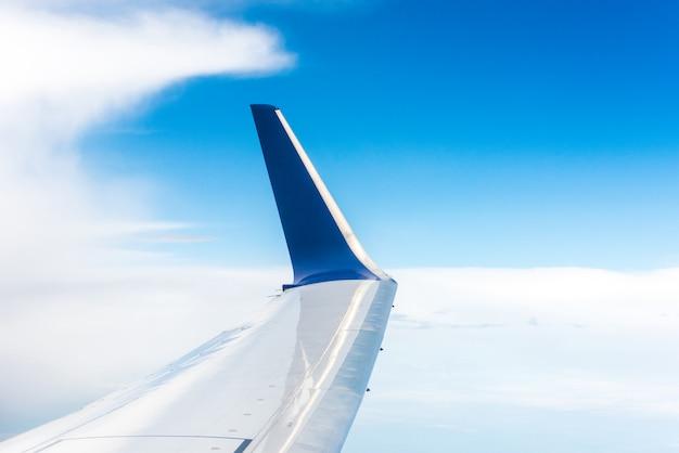 Flügel des blauen flugzeuges in der luft