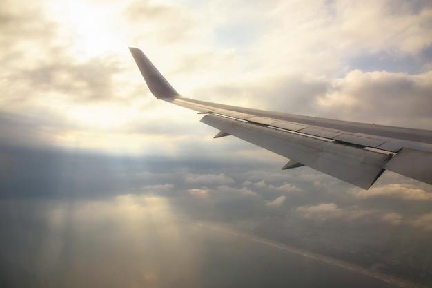 Flügel des flugzeuges mit strahlen durch wolken