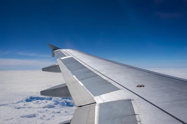 Flügel des flugzeugfliegens über den wolken im hintergrund des blauen himmels durch das fenster.