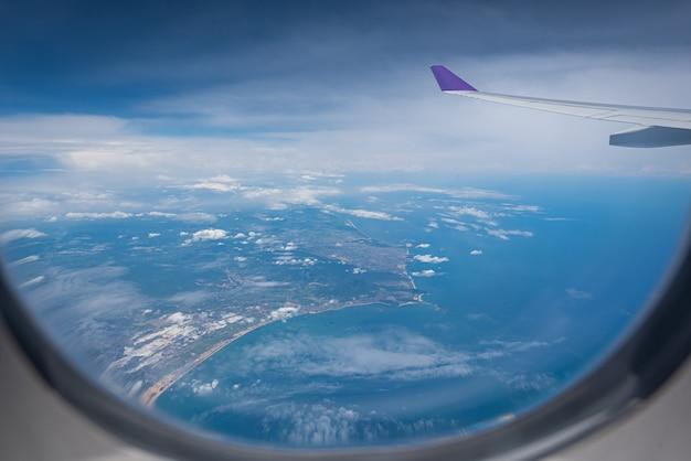 Flügel des flugzeugfliegens über hong kong-stadthintergrund durch das fenster.