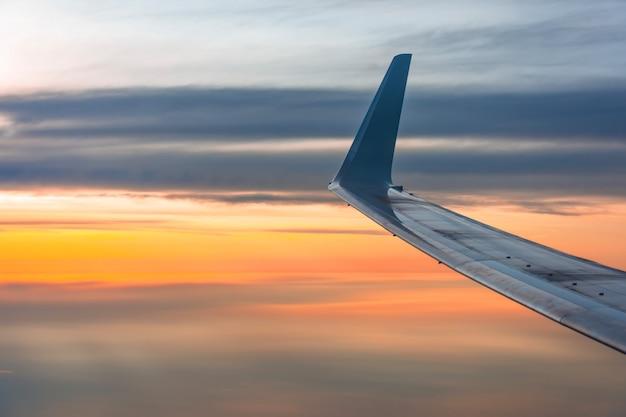 Flügel des flugzeugs beleuchtet vom sonnenaufgangshimmel.