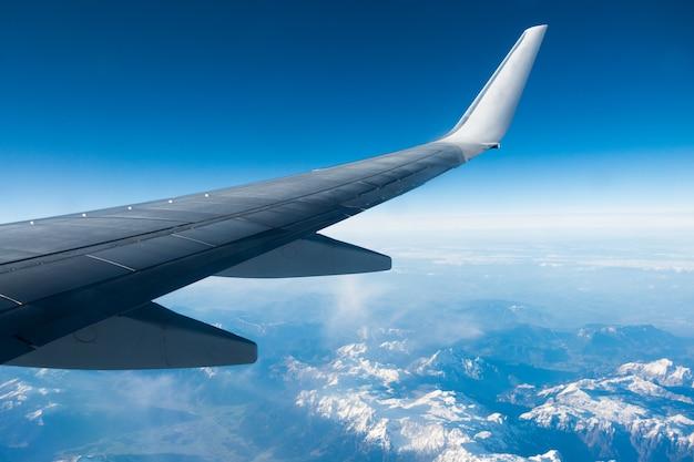 Flügel des flugzeugs fliegt über wolken und berge