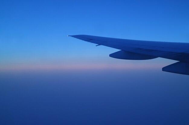 Flügel des flugzeugs gegen schönen blauen morgenhimmel während des fluges