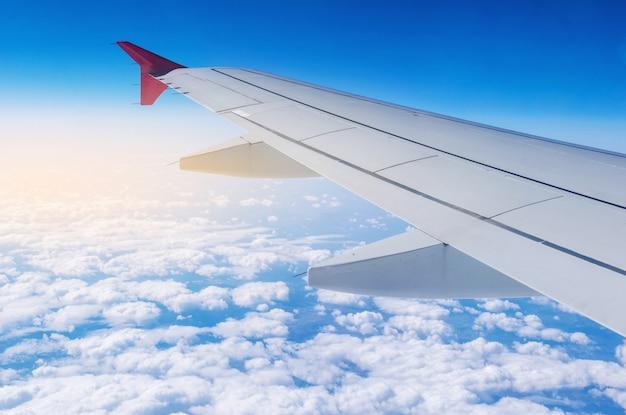 Flügel des flugzeugs im flug mit wolken. konzept von reisen und flügen in neue länder