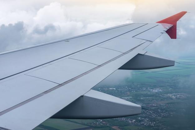 Flügel des flugzeugs im flug, umgeben von wolken