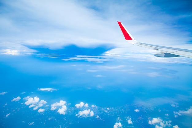 Flügel des flugzeugs mit blauem himmel und wolken