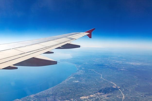 Flügel eines flugzeugs. flugzeugflügel auf den wolken