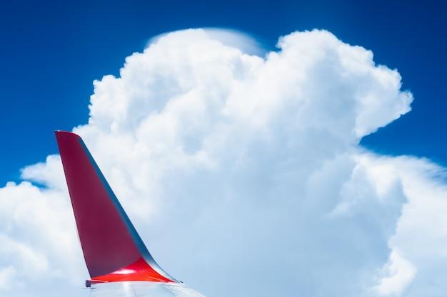 Flügel eines flugzeugs mit schönem blauen himmel und wolkenhintergrund, ansicht vom flugzeugfenster.