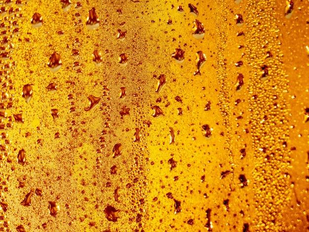 Flüssige goldene wassertropfen, gelber hintergrund