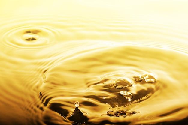 Flüssiger goldtropfen und -kräuselung, abstrakter hintergrund