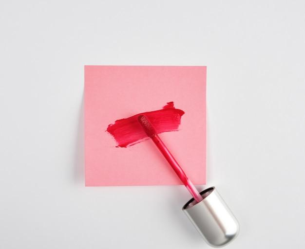 Flüssiger lippenstift und ein abstrich des roten lippenstifts auf einem rosa papieraufkleber