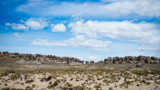 Flüssiger strom der großen höhe in der rauen unfruchtbaren landschaft mit szenischem drastischem himmel. weitwinkelansicht von oben genanntem bei 4000 m auf den andenhochländern, peru.