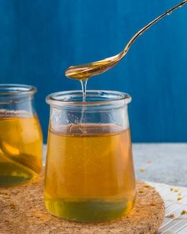 Flüssiger vorderer löffel des honigs im glastopf über dem küstenmotorschiff