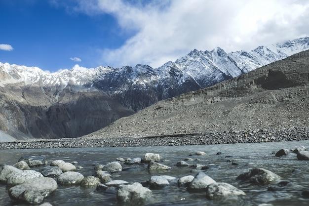 Flüssiger wasserstrom unter schnee bedeckte berge in karakoram-strecke mit einer kappe.