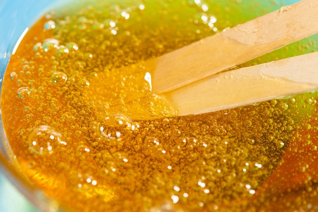 Flüssiges gelbes wachs oder zuckerpaste zur enthaarung und klebt auf blauem hintergrund. das konzept von