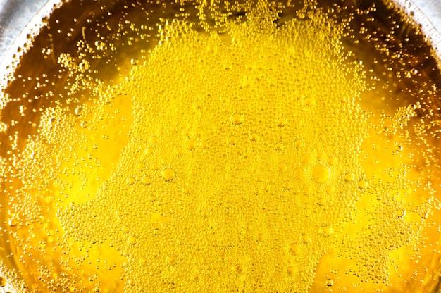 Flüssiges goldgelbes benzin sprudelt hintergrund auf bier- oder champagnerglas. nahaufnahme, makroaufnahme.