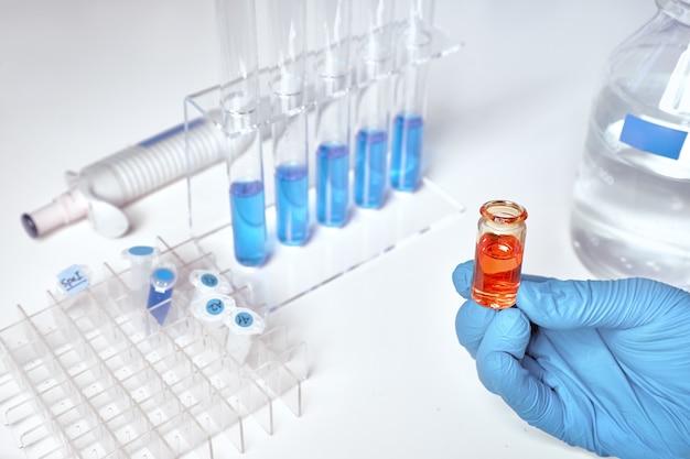 Flüssigkeitsprobe, blaue flüssigkeitsproben in glasröhrchen und schalen