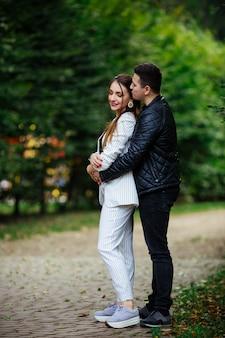 Flüstern über die liebe. hübscher junger mann, der seine schöne freundin umarmt, während er zeit zusammen in der stadt verbringt
