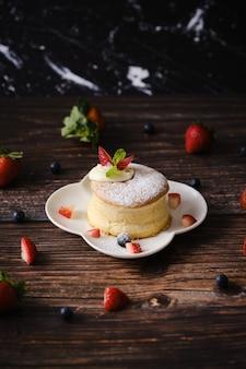 Fluffy souffle pfannkuchen mit sahne und beeren auf weißem teller auf holztisch gesetzt.