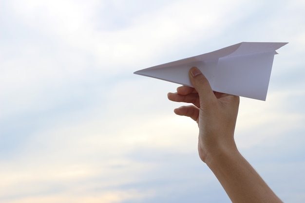 Flug nehmen! hand, die papierflugzeug im himmel hält