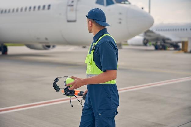 Flugbegleiter mit geräuschunterdrückenden kopfhörern und einem paar zauberstäben mit blick auf das gelandete flugzeug