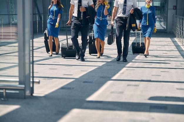 Flugbegleiter und piloten tragen trolleys und gehen zum ausgang des flughafenterminals