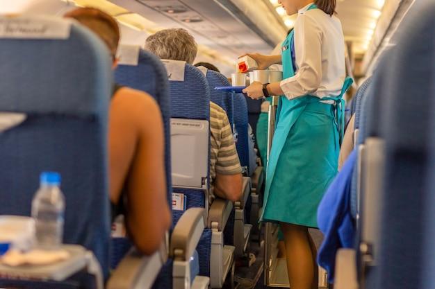 Flugbegleiterin serviert den passagieren getränke an bord.