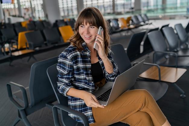 Flughafen junge passagierin mit smartphone und laptop sitzen in der terminalhalle, während sie auf ihren flug wartet