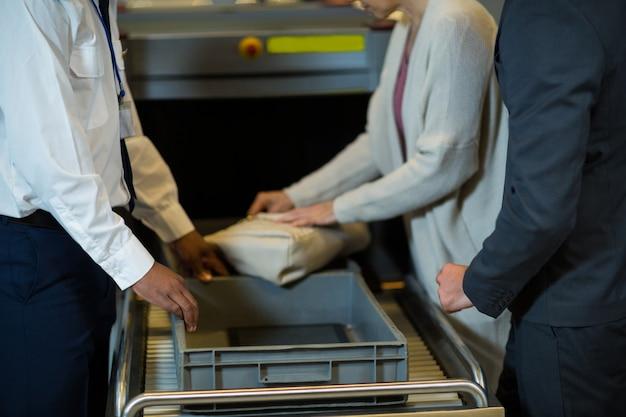 Flughafen-sicherheitsbeamter, der tasche des pendlers prüft