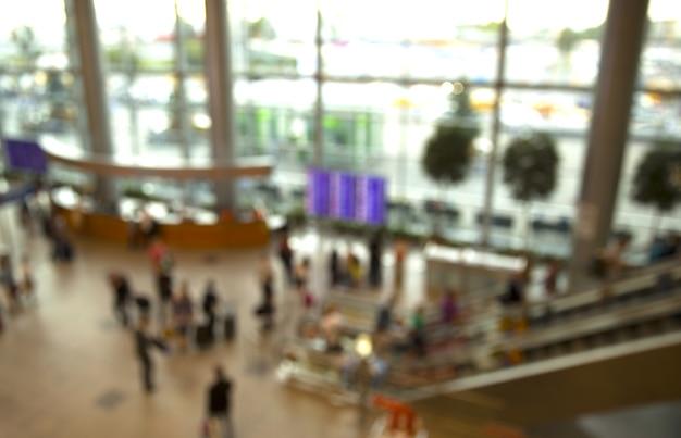 Flughafen. verschwommene leute in der hauptlobby schlossen, um den angekündigten schreibtisch zu fliegen.