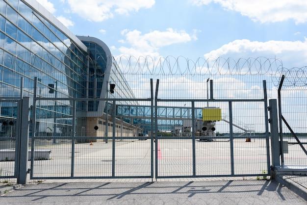Flughafenzaungitter auf dem hintergrund der passagierbrücken zum einsteigen der passagiere. für den test auf die platte legen.