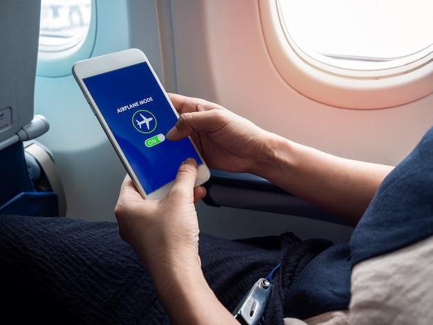 Flugmodus-konzept. hand hält weißes smartphone und schaltete den flugzeugmodus auf dem bildschirm in der nähe des fensters im flugzeug ein.
