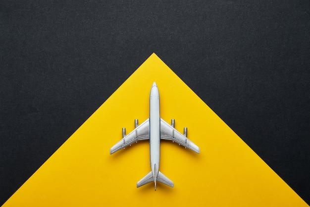Flugreisekonzept mit flugzeug und gelb mit schwarzem hintergrund mit kopienraum und draufsicht.