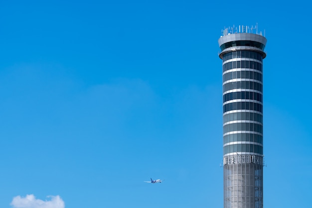 Flugsicherungsturm im flughafen mit internationalem flugflugzeug, das auf klarem blauen himmel fliegt. flughafen verkehrskontrollturm zur kontrolle des luftraums per radar. luftfahrttechnik. flugmanagement.