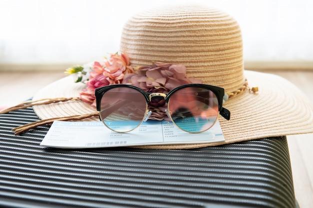 Flugtickets, sonnenbrillen, frauenhut sind auf dem gepäck, der sommerzeit und dem feiertagskonzept.