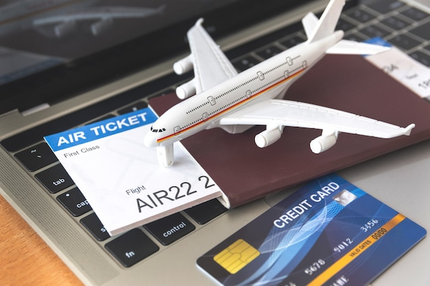 Flugtickets und pässe in der nähe von laptop und flugzeug auf dem tisch. online-ticketbuchungskonzept