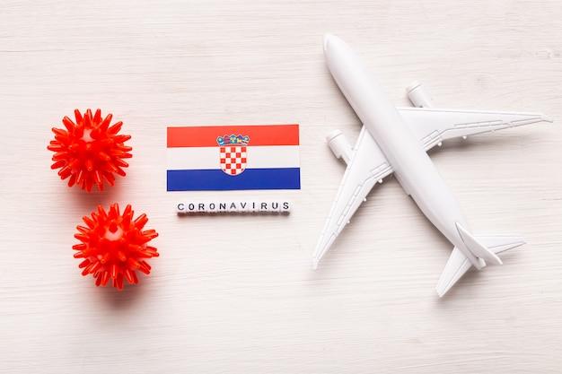 Flugverbot und geschlossene grenzen für touristen und reisende mit coronavirus covid-19. flugzeug und flagge von kroatien auf einem weißen hintergrund. coronavirus pandemie.