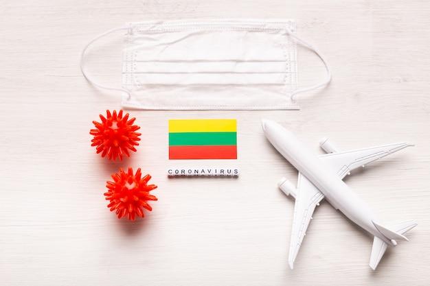 Flugverbot und geschlossene grenzen für touristen und reisende mit coronavirus covid-19. flugzeug und flagge von litauen auf einem weißen hintergrund. coronavirus pandemie.