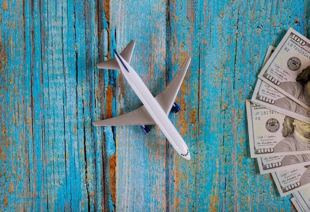 Flugzeug auf dollarbargeld mit notizbuchreise mit flugzeug