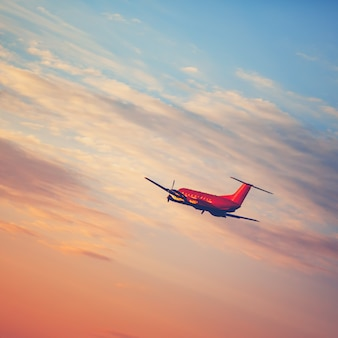 Flugzeug, das am sonnenunterganghimmel abhebt