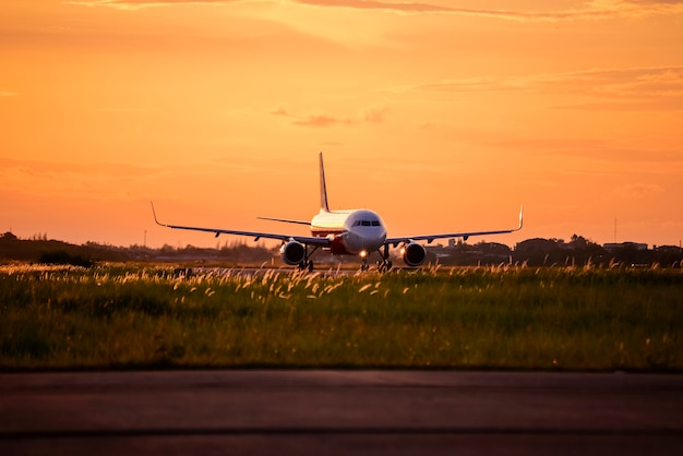 Flugzeug, das auf rollbahn bei sonnenuntergang läuft.