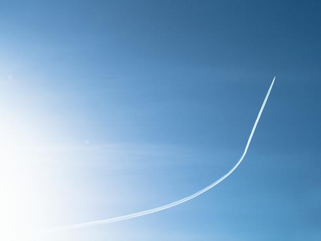 Flugzeug, das oben fliegt und spur am blauen himmelhintergrund verlässt