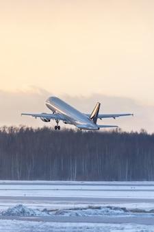 Flugzeug, das während eines sonnenuntergangs im winter abhebt. luftfahrtkonzept