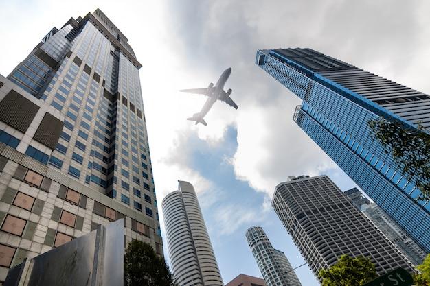 Flugzeug fliegt tief über hochhausbürogebäude